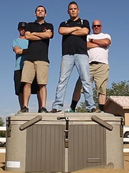 Picture of four men standing on top cover of the hardcover spa showing its durability